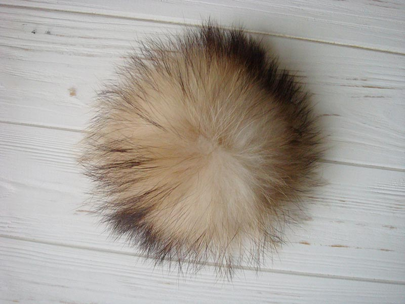 white yellow and black raccoon fur pom pom